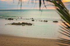 Die azurblaue Küste, der Strand auf der Insel von Thailand, der Sonnenuntergang, die Felsen durch das Ufer und die unscharfe Palm stockfotos
