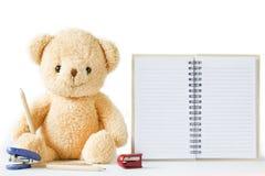 Die Bärnpuppe, die sitzt, Bleistiftnotizbuch halten auf weißem Hintergrund, ist Stockfoto