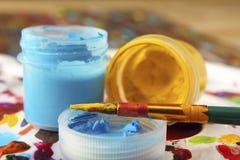 Die Bürste wird mit gelber Farbe auf dem Hintergrund von farbigen Dosen mit Acrylfarbe geschmiert Nahaufnahme Schärfe auf Bürste Stockfoto
