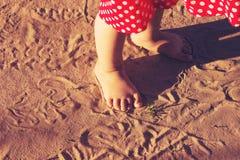 Die Babyfüße, die auf Sand gehen, setzen bei Sonnenuntergang auf den Strand getont Stockfoto