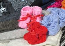 Die Babyschuhe und die Socken des Babys gemacht von der Wolle unter der Sonne Lizenzfreie Stockfotografie