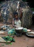 Die Baka Frau zerstößt ein Mehl in einem Mörtel. Stockfotografie