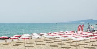 Die Balchik-Küste, Strand mit Sanden, Sonnenschirme und blaues Wasser Lizenzfreies Stockbild