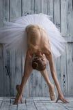 Die Ballerina, die im weißen Ballettröckchen gekleidet wird, macht mageres Vorwärts stockfoto
