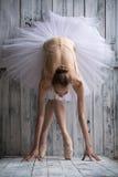 Die Ballerina, die im weißen Ballettröckchen gekleidet wird, macht mageres Vorwärts stockbilder