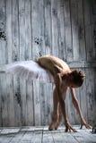 Die Ballerina, die im weißen Ballettröckchen gekleidet wird, macht mageres Vorwärts lizenzfreie stockfotos