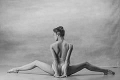 Die Ballerina sitzt mit ihren zurück Beinen weit auseinander stockfotografie