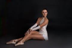 Die Ballerina sitzt und hat einen Rest stockbild