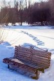 Die Bank im Park unter den schneebedeckten Banken wird durch die Strahlen der Einstellungsmärz-Sonne belichtet Hinter den Abdrück Stockbilder
