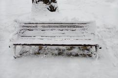 Die Bank im Park wird mit Schnee bedeckt stockfotos