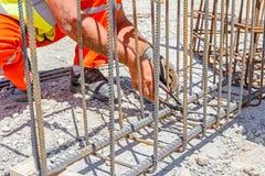 Die Bauarbeiter, die Rebar für binden, verstärken konkrete Spalte stockfotografie