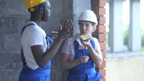 Die Bauarbeiter machen eine Pause ein Sandwich und ein Plaudern essend stockbilder