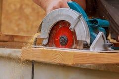 Die Bauunternehmerarbeitskraft, die Hand- Schneckengetrieberundschreiben verwendet, sah, um Bretter auf einem neuen Haupt-constru lizenzfreie stockfotografie