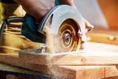 Die Bauunternehmerarbeitskraft, die Hand- Schneckengetrieberundschreiben verwendet, sah, um Bretter auf einem neuen Haupt-constru stockfotos