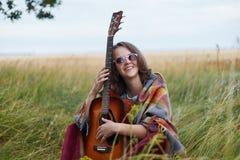Die begabte junge Frau kleidete Gitarre zufällig halten breit draußen lächelnd an der Kamera, die gute Laune, um Rest zu haben ha Stockfoto