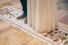 Die Beine der Braut und des Bräutigams werden auf gesticktem Tuch, traditionsgemäß an einer Heiratszeremonie in der Kirche lizenzfreies stockfoto