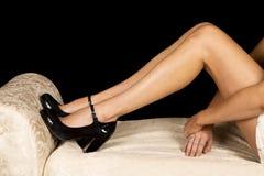 Die Beine der Frau auf Bank folgt herauf Schwarzes auf den Fersen Stockfotos