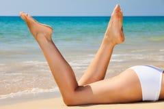 Die Beine der Frau auf dem Strand Stockbild