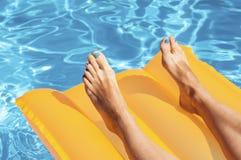 Die Beine der Frau auf einer Matratze in einem Pool Stockfotos
