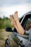 Die Beine der Frau aus dem Auto heraus Stockfotos