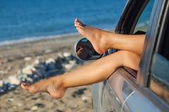 Die Beine der Frau, die heraus ein Autofenster baumeln Lizenzfreies Stockfoto