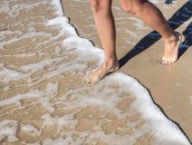 Die Beine der Frau, die in das Meer treten Lizenzfreies Stockfoto