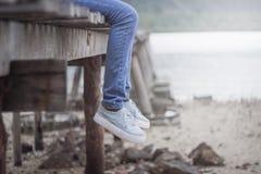 Die Beine der Frau, die an der alten Holzbrücke hängen Die einsame Tonweinleseart mögen nicht andere Lizenzfreie Stockbilder