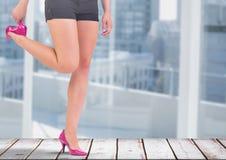 Die Beine der Frau im Rock und in den hohen Absätzen durch Fenster des Büros Lizenzfreies Stockfoto