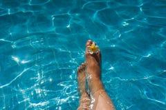 Die Beine der Frau mit Blume im blauen Pool Stockbilder