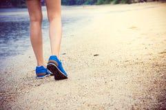 Die Beine der Frauen, die entlang den Strand laufen oder gehen Stockfotografie