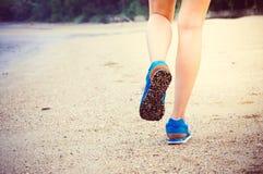 Die Beine der Frauen, die entlang den Strand laufen oder gehen Lizenzfreies Stockfoto