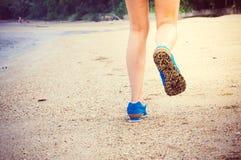 Die Beine der Frauen, die entlang den Strand laufen oder gehen Stockfoto