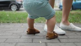 Die Beine der Mutter und erste Schritte ihres kleinen Sohns stock video footage