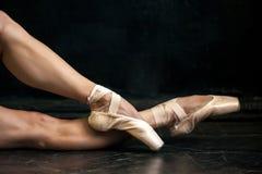 Die Beine der Nahaufnahmeballerina in den pointes auf dem Schwarzen Lizenzfreie Stockfotografie
