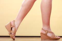 Die Beine der Nahaufnahmefrau mit braunen Schuhen des hohen Absatzes Stockfotos