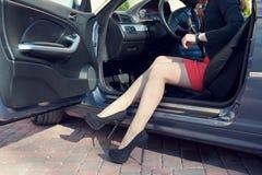 Die Beine der schlanken Frauen aus dem Auto heraus Stockfotografie