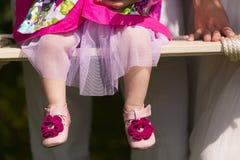 Die Beine des kleinen Mädchens auf dem Schwingen Stockfotos