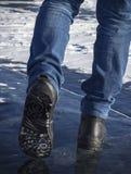 Die Beine des Mannes im Schwarzen, das in Schnee geht lizenzfreies stockfoto