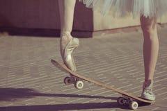 Die Beine einer Ballerina auf einem Skateboard stockbild