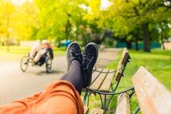 Die Beine einer Frau, die auf einer Bank liegt Stockbilder