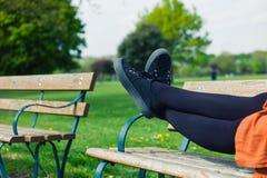 Die Beine einer Frau, die auf einer Bank liegt Lizenzfreies Stockbild