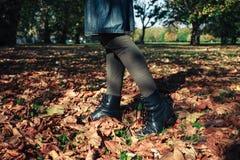 Die Beine einer Frau, die in gefallene Blätter geht Stockbild