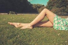 Die Beine einer jungen Frau, die im Gras liegt Lizenzfreie Stockfotografie
