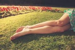 Die Beine einer jungen Frau, die im Gras liegt Lizenzfreies Stockbild