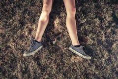 Die Beine einer jungen Frau, die in Th egrass liegt Lizenzfreies Stockfoto