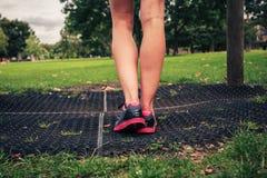 Die Beine einer jungen Frau durch Eignungsausrüstung Stockfotos