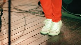Die Beine einer Musikernahaufnahme, die zur Musik am Konzert aufprallt stock video