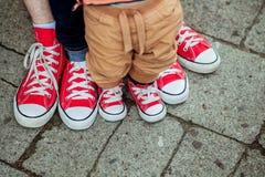 Die Beine und die Füße der Kinder in den Turnschuhen Stockfotos