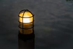Die Beitragslampe mit unscharfem Wasserhintergrund Stockfotografie