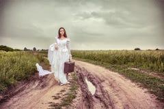 Die beleidigte Braut, die mit einem alten Koffer geht Stockfotografie